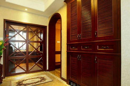 玄关屏风隔断效果图8 玄关过道的设计以棕红色和荧光黄为主,荧光黄的天花板和墙壁,荧光黄的菱形大理石地板,正前方是一个棕红色木质框架的玻璃推拉门,使两个房间隔开,紧挨着推拉门,在房间的右侧有一个圆拱形棕红色木质边框门,门的旁边是一组嵌入墙壁的深棕色木质置物柜,再加上一盆大型植株的调和,整个房间充满古典气息。