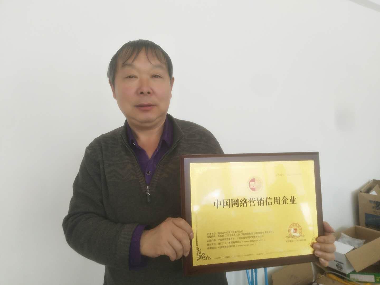 网站负责人合影中国网络营销信用企业牌匾